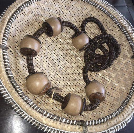 Colar para decorar mesas feito com bolas de barro cozido e discos de coco.